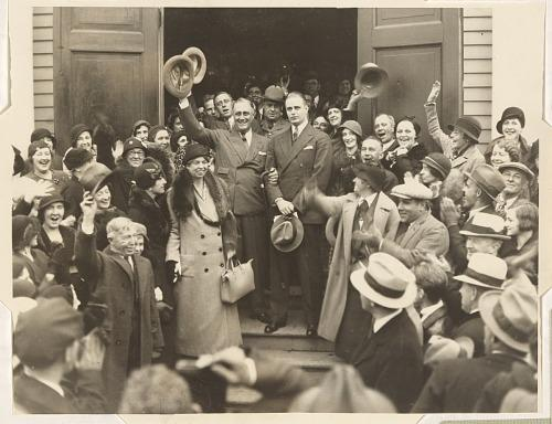 Roosevelt exiting building with his wife and son, applauded by citizens.