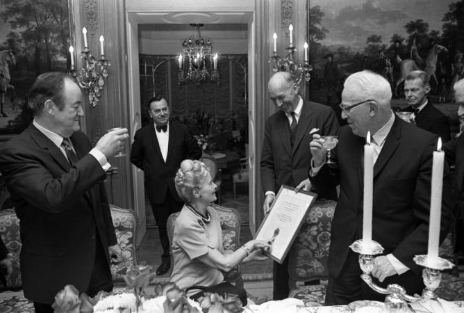 Post sitting at a table with the Regents and the Secretary standing, smiling, and toasting.