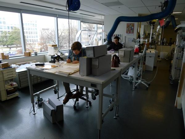 The blog author and another man sit at work stations in the conservation lab.