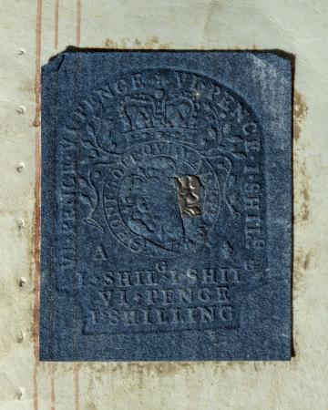 A blue rectangle of paper is embossed with the British royal motto circling a stylized flower surmou