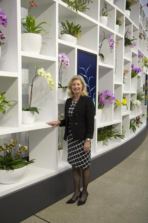 Barbara Faust stands in front of a display of orchids.