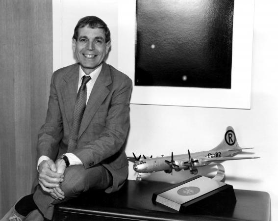 Harwitt leans sits/leans on his desk next to a model of an airplane.