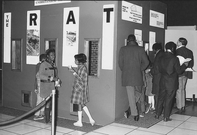People explore the exhibit The Rat. Visible are three panels labeled R, A, and T. Men and children a