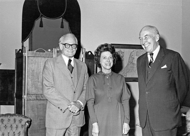Two men and one woman stand in a room.