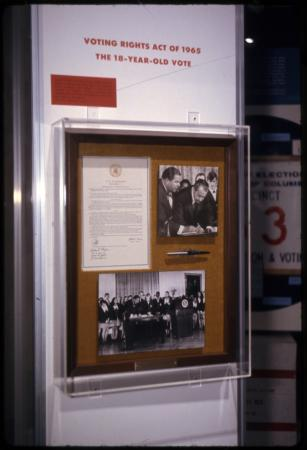 Pen on display alongside a document and a photograph of Nixon signing something.