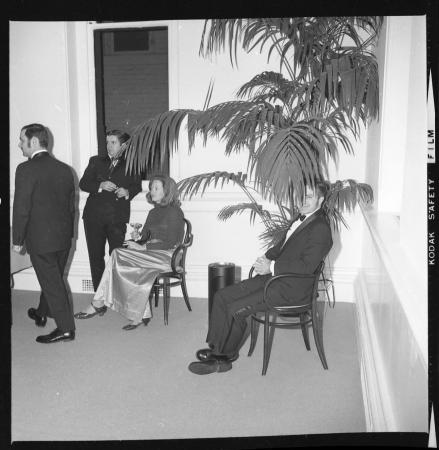 A man and woman sit in chairs. The man is partly covered by a large plant.