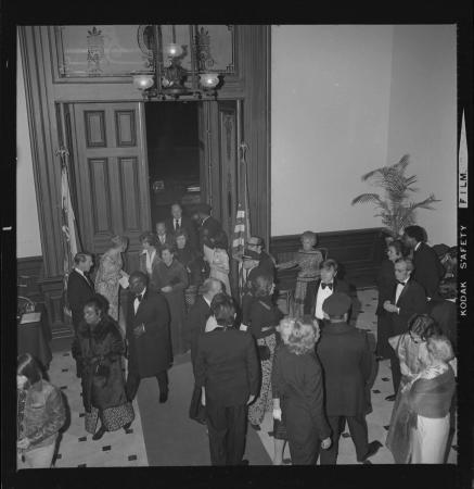 A large crowd of people gathers at an entry way in a building. They are wearing formal attire