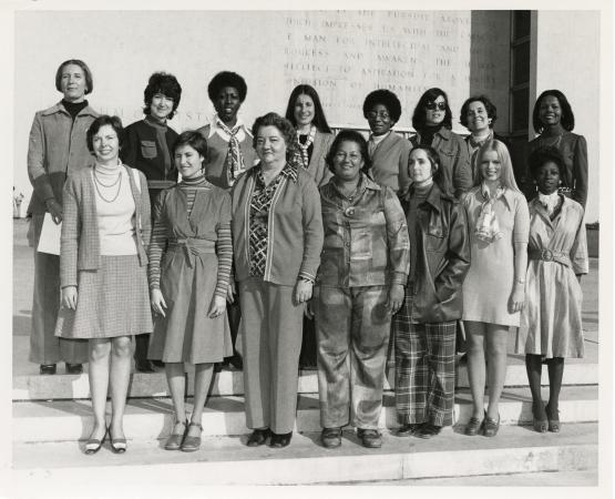 Fifteen women stand on the steps in front of the Smithsonian National Museum of American History.