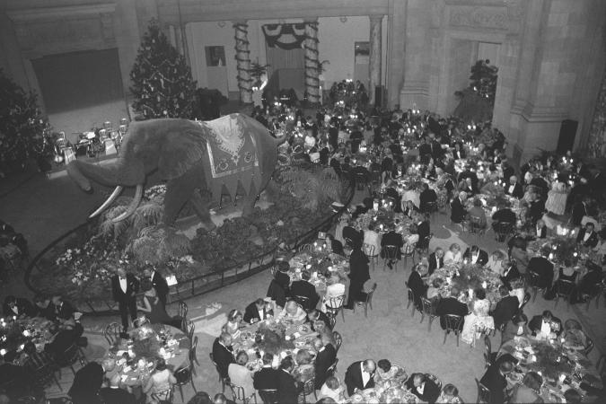 Photograph of men and women eating at round tables, taken from above. A large taxidermied elephant i