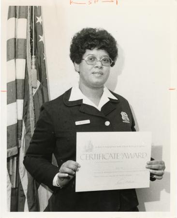 A woman wearing a white polo and dark sweater and a badge smiles at the camera and holds a certifica