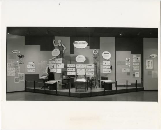 A black and white photograph featuring a wide shot of one of the exhibits on view feature Rube Goldb