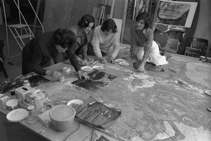 Four women work on a mosaic on some sort of base.