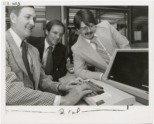 Three men test out new computer equipment. They are all wearing suits.
