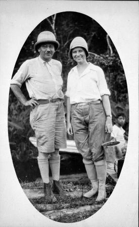 Lucile Mann, dressed in high socks, boots, and slacks, stands next to her husband in British Guiana