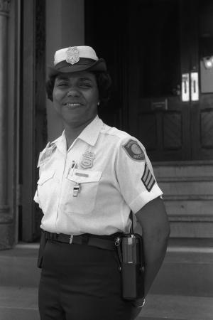 A woman in a guard uniform, with hat, smiles at the came. Steps and a door are in the background.