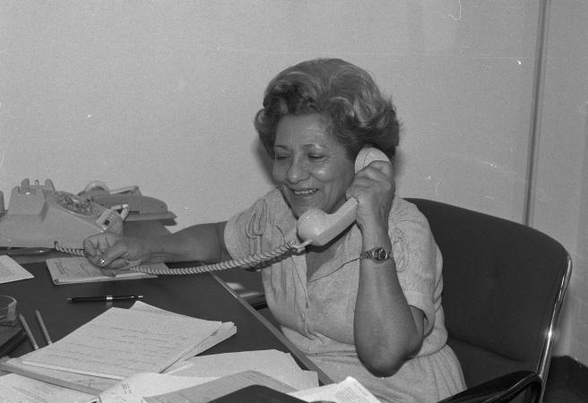 Adela Gomez sits at her desk posing with her phone in hand.