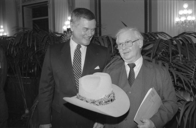 """Larry Hagman holds up a """"cowboy"""" hat and stand next to another man."""