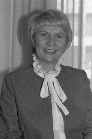 Portrait photograph of a white woman with short hair and a long, white neck scarf.