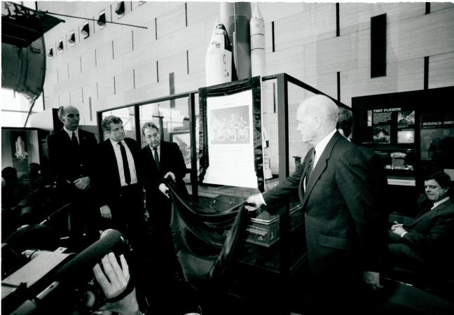 People stand around a plaque, being unveiled.