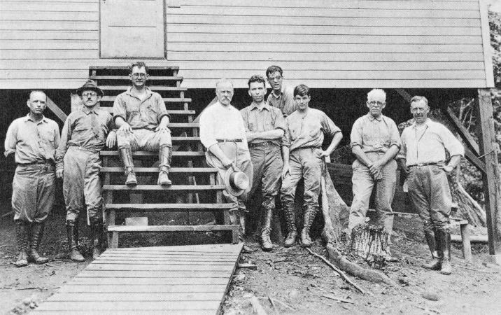 A group of nine men stand outside a structure on Barro Colorado Island.