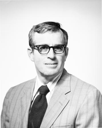 Portrait of Porter M. Kier. He is wearing a suit, tie, and thick-framed glasses.