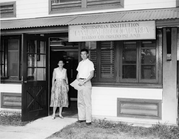 Adela Gomez and Carl Koford stand in the doorway of the new building under the sign Smithsonian Inst