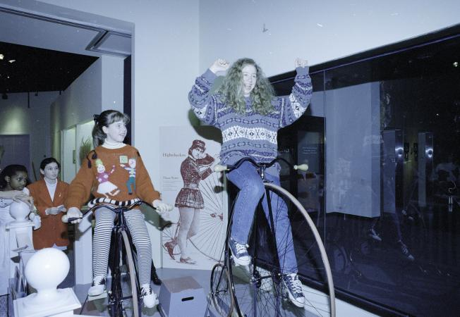 Chelsea Clinton sits on a high wheeler and another young woman sits on a shorter bike. Other childre