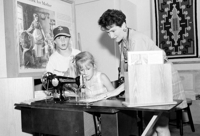 A woman and two children work with a sewing machine on a table.