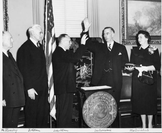 A man raises his hand at a podium surrounded by other people are are formally dressed.