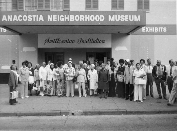 "A group of men and women stand outside of a theater labeled ""Anacostia Neighborhood Museum."""