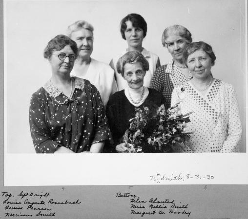 A group of five women stand around an elderly woman holding a bouquet of flowers who is retiring.