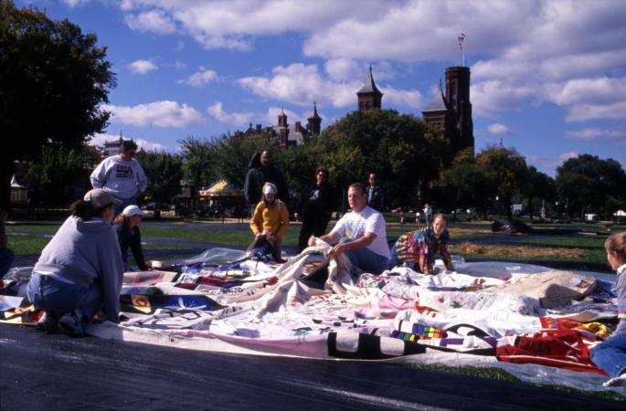 People spreading out quilt panels with the Smithsonian Castle in the background.