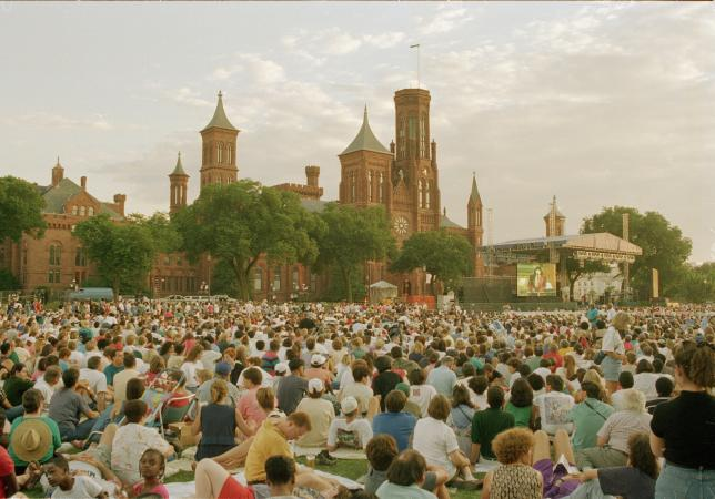A crowd sits on the Mall facing a stage in front of the Smithsonian Institution Building.