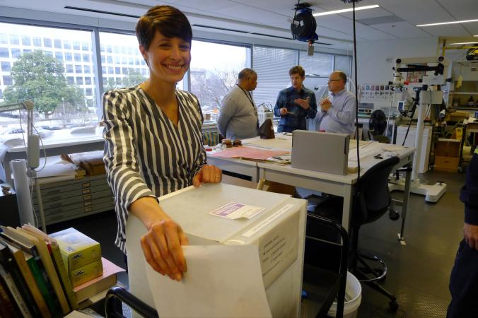Alison smiles toward the camera and holds up a box labeled