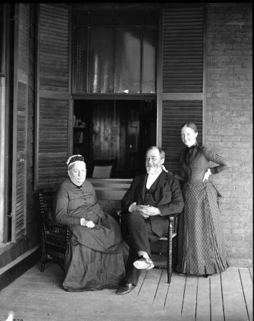 Spencer and Mary Baird sit in chairs and Lucy Baird stands behind her father.