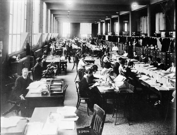 Men and women sit closely at desks that hold piles of paper.