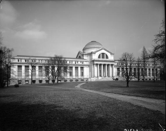 A view of the National Museum of Natural History in 1911. There is a horse and carriage near the ent