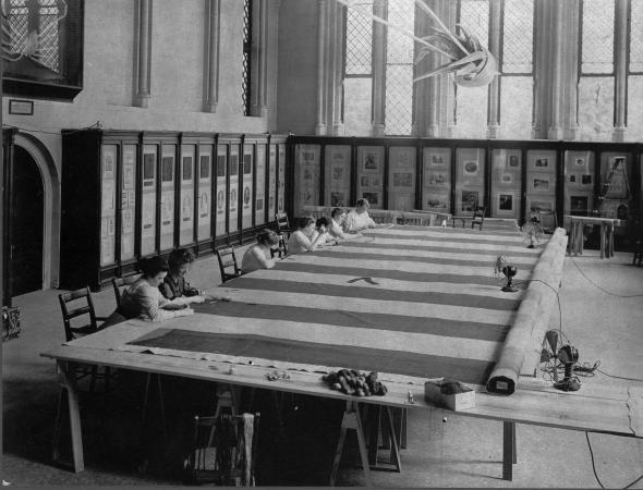 Women at work repairing the Star-Spangled Banner on a set of makeshift tables in the room in the Cas