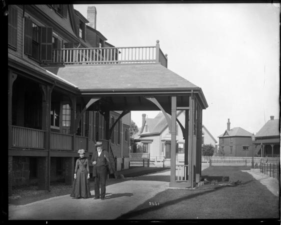 Spencer and Lucy Baird walk on a pathway outdoors. Both are wearing fairly formal attire.