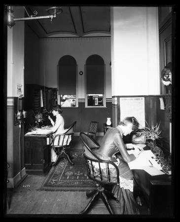 Two woman in long dresses sit and work at desks.