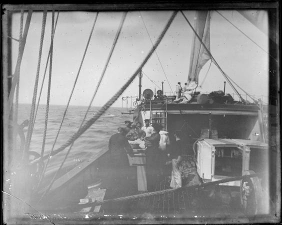 People work on the deck of the Albatross. The ship is sailing on a body of water.