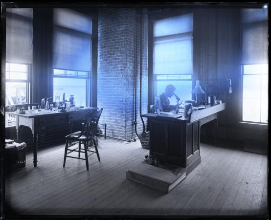 A man sits at one of two desks in a lab. Light comes in from the windows, which appears to give the