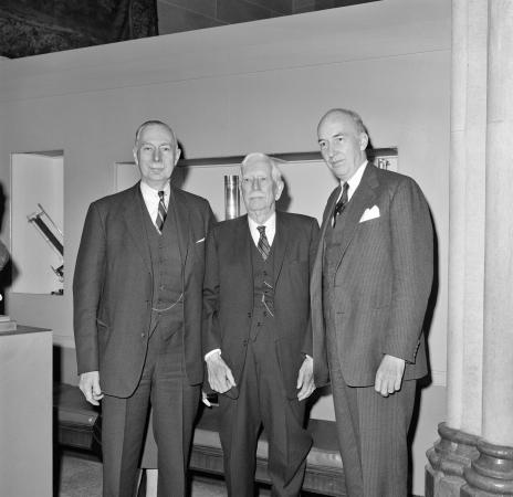 Three men in suits stand in a room.
