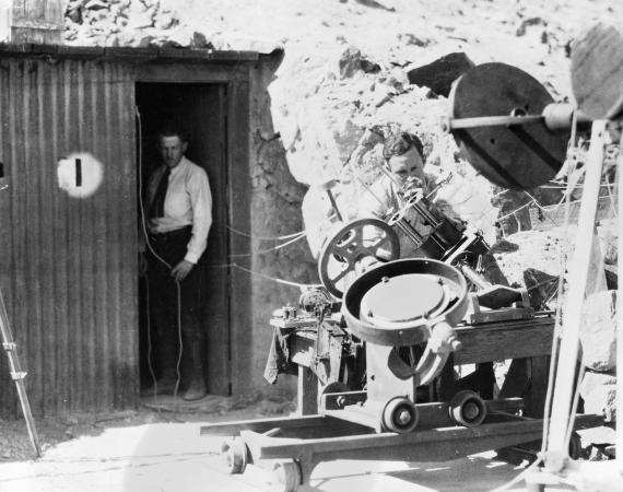 Black and white photo of one man at the entrance to the Mount Montezuma Observatory cave and another