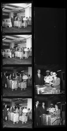6 black and white negatives of security staff and men in suits around large boxes on carts with whe