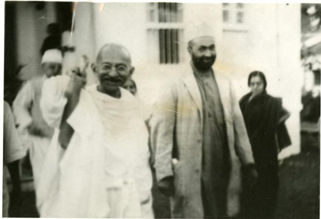 Gandhi and another person walk. Gandhi waves at the camera.