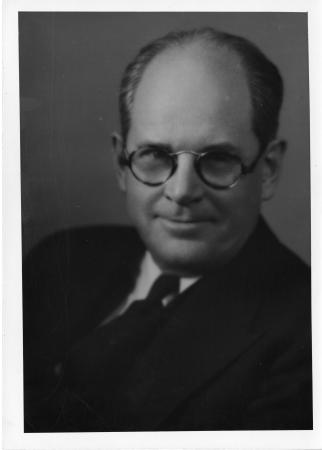 Portrait of Darling. He is wearing a suit and tie and thick, round glasses.