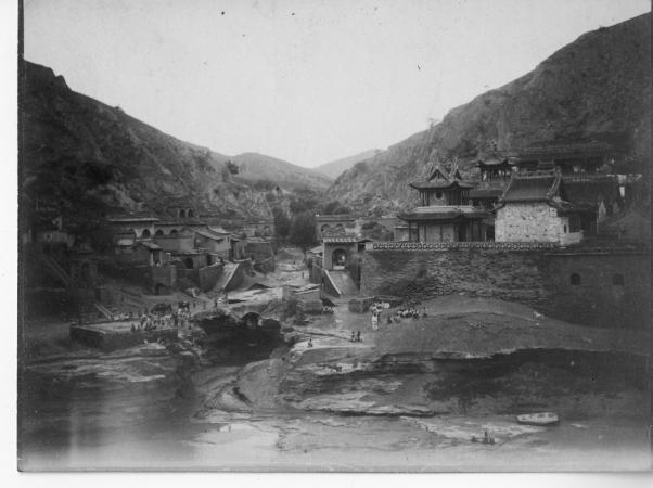 Black and white photograph of a village with various structures on a hilltop.