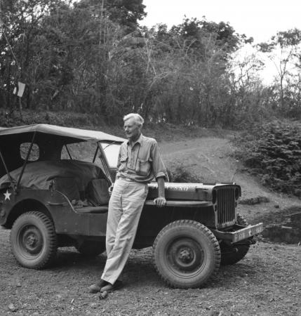 A man leans against a jeep on a dirt road. Trees are in the background.