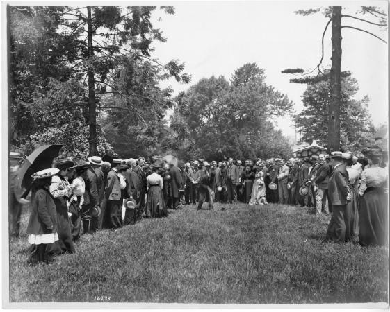 Men and women in nice clothes stand around a field. A man is standing at the center and digging into
